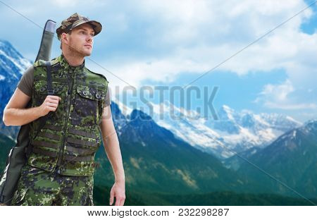hunting, army, military service and people concept - young soldier, ranger or hunter with gun over mountains background