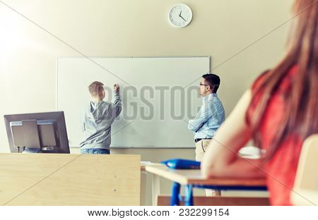 education, high school, learning and people concept - student boy writing something on blank white board and teacher in classroom