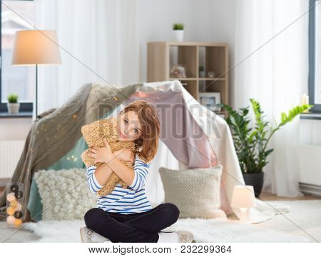 childhood and people concept - cute little girl hugging teddy bear at home over kids room and tepee background