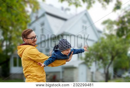family, childhood, fatherhood, leisure and people concept - happy father and little son playing and having fun outdoors over house background