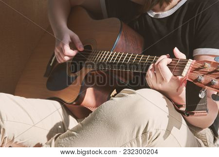 Young Girl Playing Guitar And Sitting On The Bed With Sunshine