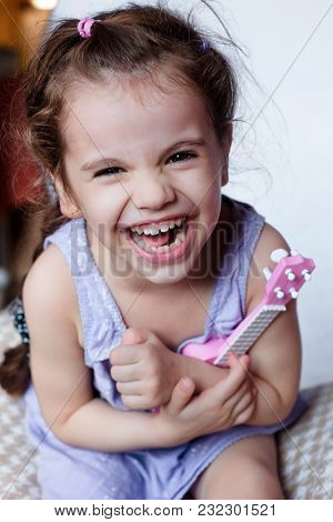Happy Little Girl Having Fun Playing With Toy Guitar Or Ukulele