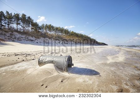 Old Trash Can On A Beach, Environmental Pollution Concept.