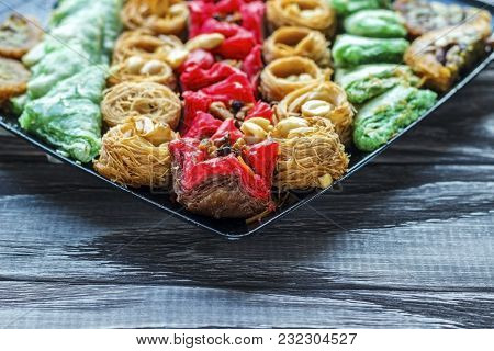 Turkish Dessert. Oriental Sweets With Nuts And Honey On A Wooden Background.