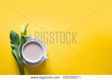 Cup Of Coffe With A Yellow Tulips Over Yellow Background, Copy Space