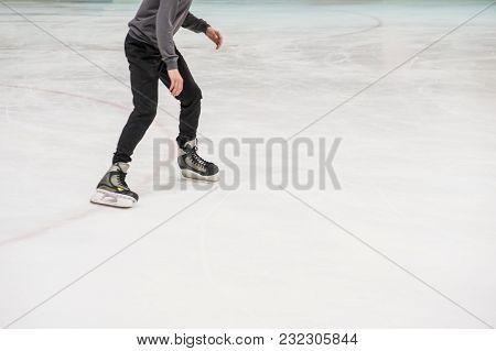 Cropped Shot Of Boy In Skates Ice Skating On Rink