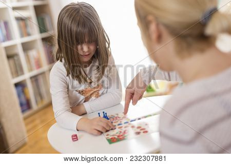 Mother And Daughter Sitting In A Playroom, Playing A Ludo Game; Daughter Repositioning The Pawn