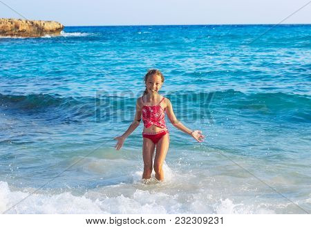 Cute Teen Girl Playing In Sea Waves. Jump Accompanied By Water Splashes. Summer  Day, Happy Childhoo