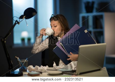 Beautiful mature business woman workaholic tired working in the office until the night on overtime