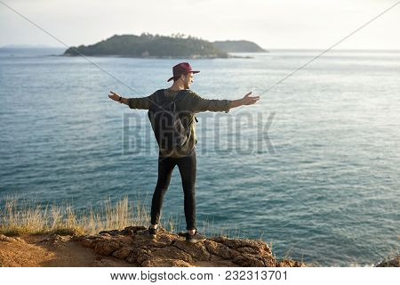 Attractive Man With A Black Backpack Stands With Outstretched Arms On The Cliff On The Sunny Backgro