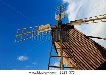 A Low Angle View Of An Old Brown Wooden Windmill.