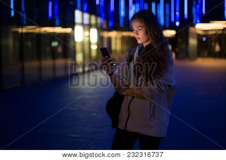 Beautiful Young Stylish Woman Walking In The Night City Streets Using Modern Smartpone, Hipster Fema