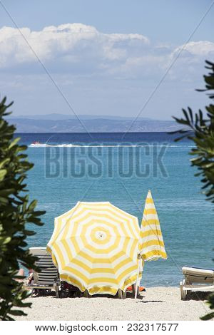 Mediterranean Beach With The Yellow Umbrellas And Deckchairs