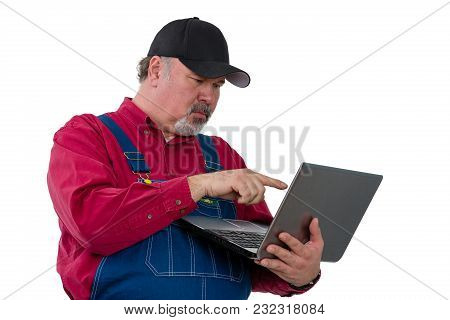 Adult Male Worker Wearing Dungarees Using Laptop While Standing Against White Background