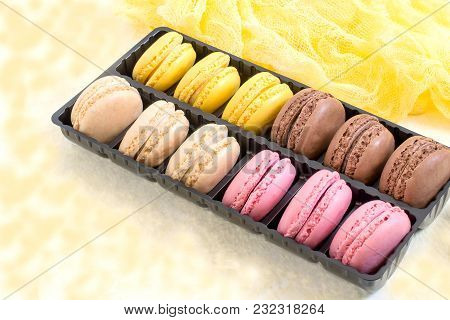 Different Macaroon In Box On Light Yellow Background With Yellow Gauze Napkin. Delicious And Sweet A