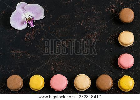Different Macaroon And Orchid On Dark Background. Delicious And Sweet Almond Cookies Macaroon With C