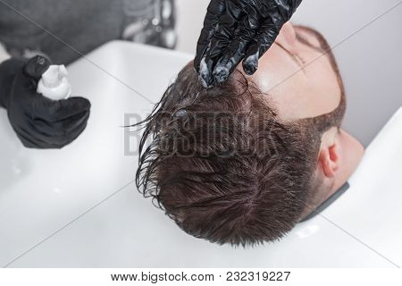 The Hairdresser Paints Hair From Gray Hair Of A Man In A Barbershop.