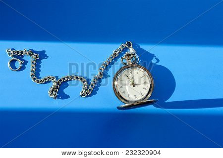 Vintage Pocket Watch On Chain On Blue Background