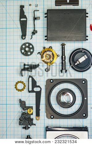 Parts Are Completely Disassembled Old Retro Film Slr Camera On Graph Paper, Close-up