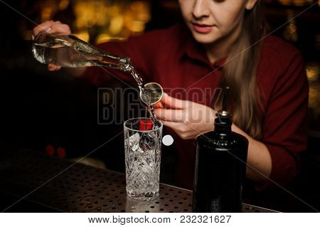 Female Bartender Pouring Gin Into A Cocktail Glass For Making A Bitter Fresh Summer Drink