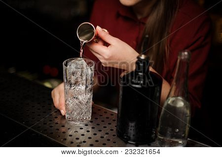 Female Bartender Pouring Some Gin Into A Cocktail Glass For Making A Bitter Fresh Summer Drink