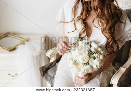 Bride In A White Wedding Dress Holding Tender Bouquet. Bridal Boudoir.
