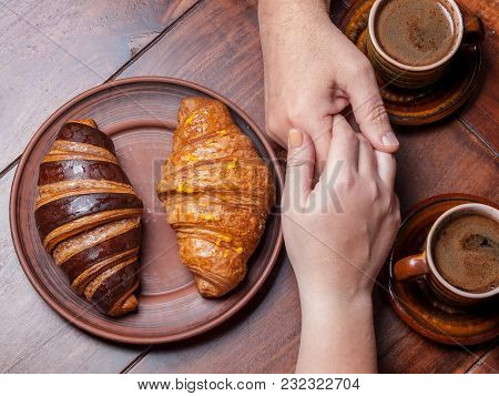 Two Croissants On A Dark Plate Near 2 Cups Of Coffee On A Wooden Dark Table,two Hands, A Touch, He A