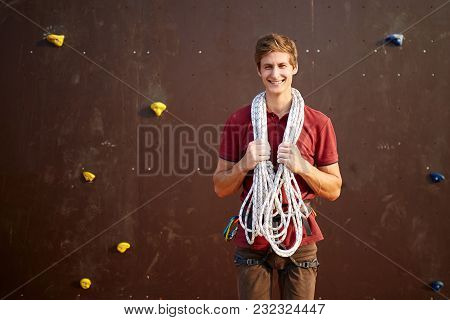Active Young Man In Sportswear Standing With Rope On Shoulders Against Artificial Training Climbing