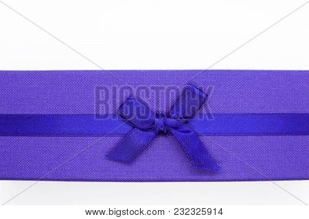 Close Up Of Violet Gift Box With Blue Ribbon On White Background With Free Space For Text. Top View