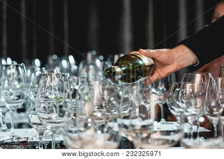 Served Table At Wine Tasting. Sommelier At Pouring White Wine From A Bottle Into Glasses