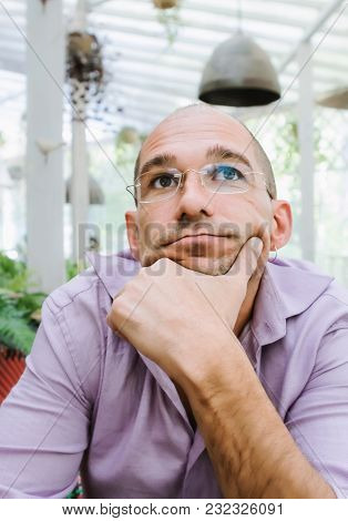Portrait Of An Attractive Thinking Bald Man Wearing Glasses In A Pensive Mood, Holding His Chin With
