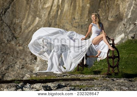 Beautiful Slim Woman Model Sits On Old Iron In Copstan. She Wears White Long Dress, Which Blows In W