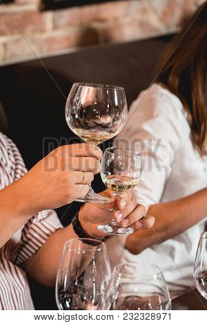 Man Holds Glass Of Wine. A Lot Of Different Wine Glasses On The Table At Wine Tasting. People Consid