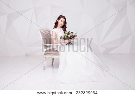 Attractive Caucasian Woman Holding A Bouquet Of Flowers In Armchair Wearing In Luxurious Wedding Dre