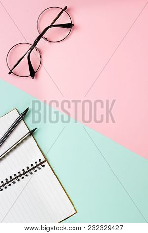 Office Concept On A Double-coloured Background. Trendy Round Glasses And A Notebook At A Workplace.