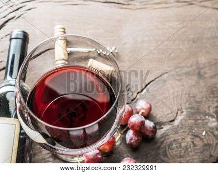 Wine glass, wine bottle and grapes on wooden background. Wine tasting.