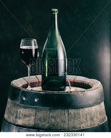 Glass of red wine and wine bottle on the oak wine keg. Vintage style.