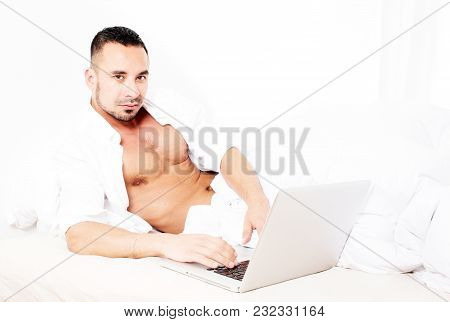 Man In White Shirt Lying In Bed With Laptop