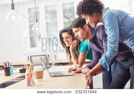 Young start-up team in coworking office is working together on laptop computer