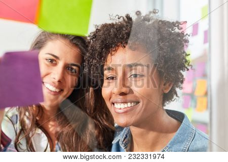 Two young women in a multicultural start-up team brainstorming together
