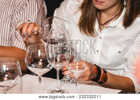 Woman Holds Glass Of Wine. A Lot Of Different Wine Glasses On The Table At Wine Tasting. People Cons