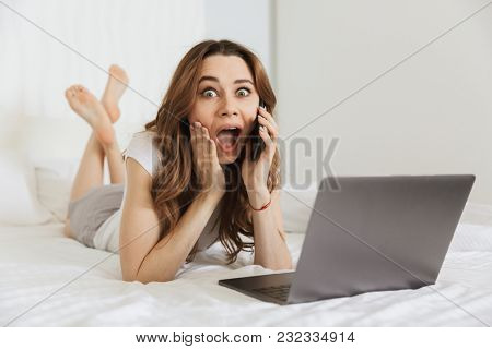 Portrait of a shocked young woman talking on mobile phone while lying in bed at home with laptop computer