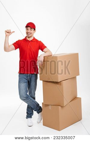 Image of a handsome happy young delivery man in red cap standing with parcel post boxes isolated over white background. Looking camera pointing.