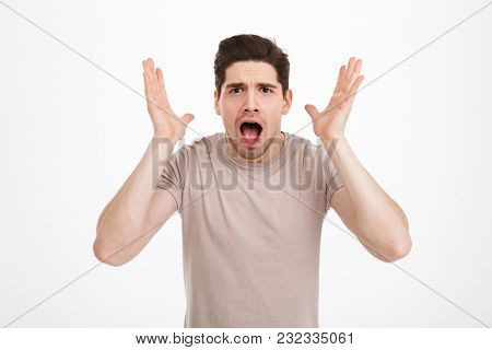 Photo of frustrated man 30s yelling and lifting hands in anger or disappointment isolated over white background