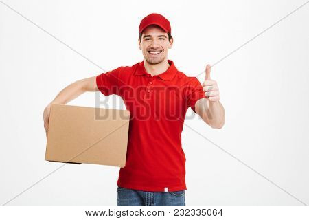 Image of a cheerful young delivery man in red cap standing with parcel post box isolated over white background showing thumbs up.