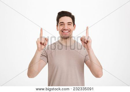 Handsome adult man 30s wearing beige t-shirt presenting copyspace text or product with gesturing fingers up isolated over white background