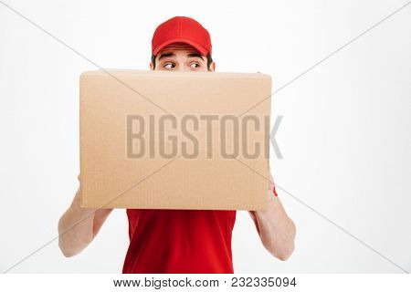 Image of a young shocked delivery man in red cap standing with parcel post box isolated over white background covering face. Looking aside.