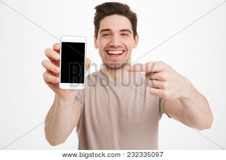 Young man in casual t-shirt demonstrating mobile phone and pointing finger on copyspace screen with pleasure isolated over white wall