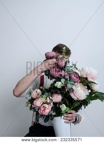 The Guy Is Holding A Bucket Of Flowers In His Hands