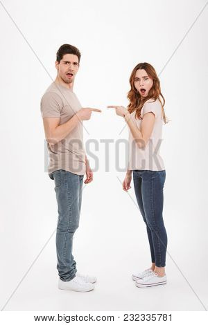 Full length photo of outraged adult guy and girl wearing beige t-shirts standing face to face and pointing fingers to each other in blaming manner over white background
